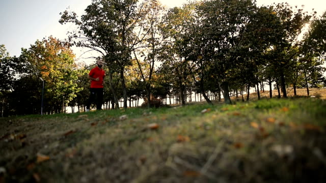 vídeos de stock, filmes e b-roll de homem novo de vista saudável que movimenta-se nas madeiras a luz solar f da manhã - só um homem maduro