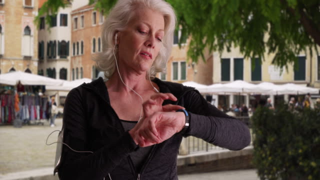 stockvideo's en b-roll-footage met healthy mature jogger checks her heart rate after run in the city - jogster