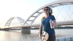 Healthy mature woman with skateboard outdoors in summer drinking water