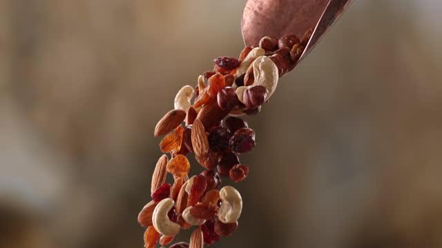 vídeos de stock e filmes b-roll de healthy mixture of nuts and berries pouring from a scoop - variação
