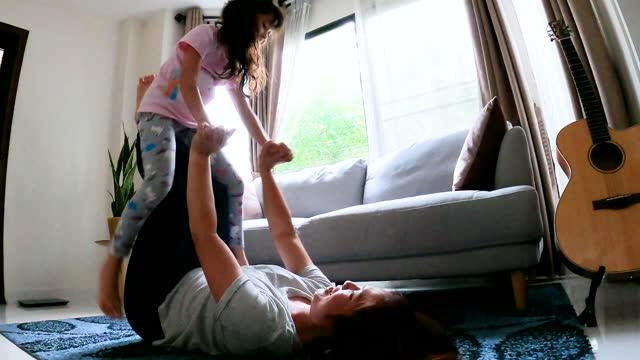 vidéos et rushes de bonheur sain de maman et de descendant et équilibre drôle de jeu dans le salon à la maison - s'entraîner