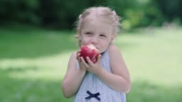 Healthy Nutrition. Child Eating Juicy Apple Outdoors