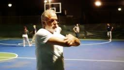 Healthy senior Latino man stretching in the evening near basketball courts in USA