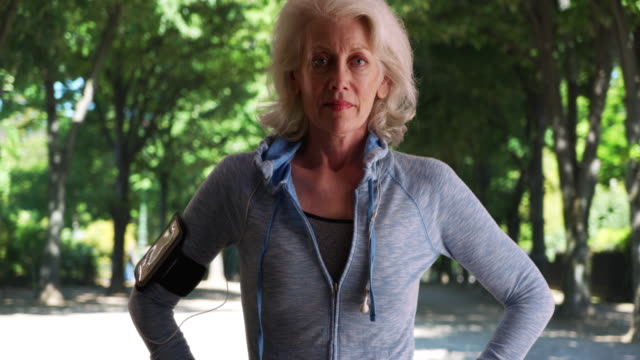 stockvideo's en b-roll-footage met healthy senior woman jogger standing in the park with hands on her hips - jogster