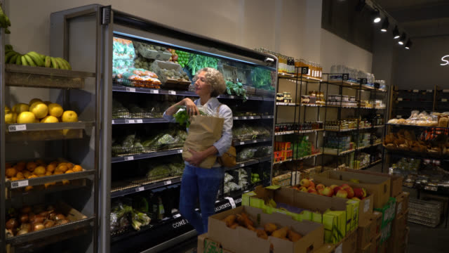 Healthy senior woman shopping at an organic food store smelling the vegetables and fruits and putting them in a paper bag