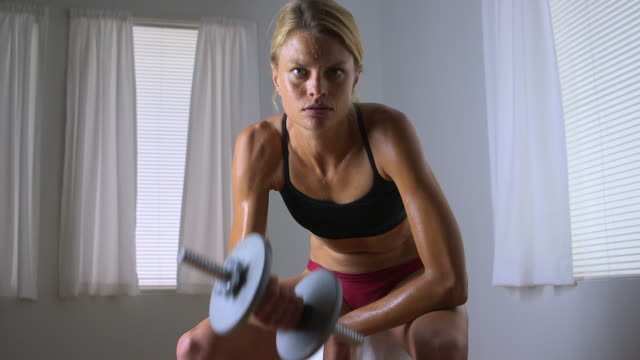 stockvideo's en b-roll-footage met healthy strong woman lifting weights - driekwartlengte