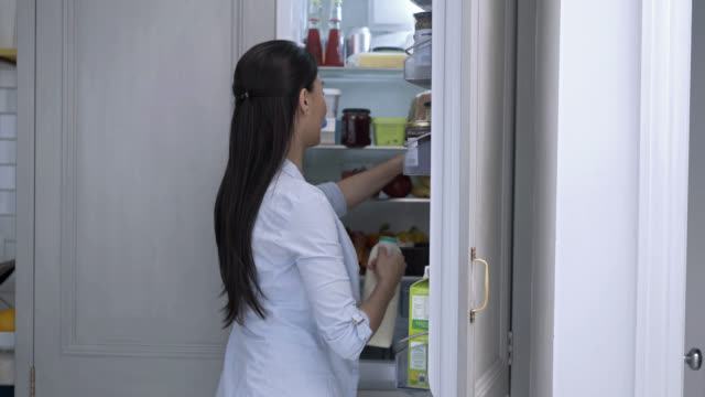 Healthy woman at home taking groceries from the fridge