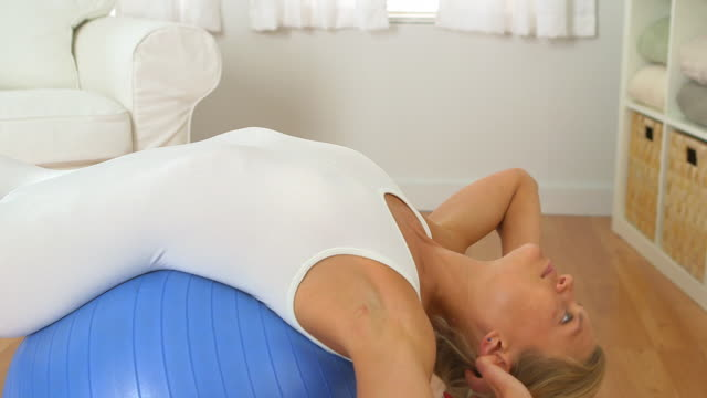 healthy woman doing crunches on exercise ball - fitness ball stock videos & royalty-free footage