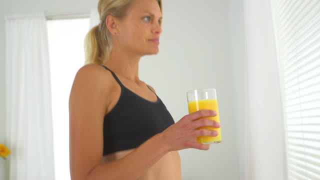 vídeos de stock e filmes b-roll de healthy woman drinking orange juice wearing active wear - só mulheres de idade mediana
