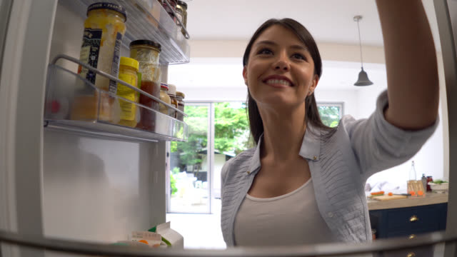 healthy woman taking food from the fridge for her breakfast - refrigerator stock videos and b-roll footage