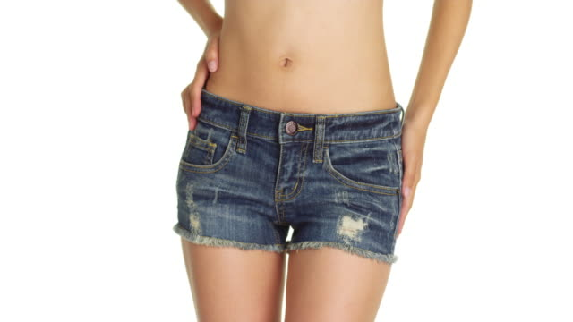 healthy woman wearing cute denim shorts - bauchnabel stock-videos und b-roll-filmmaterial