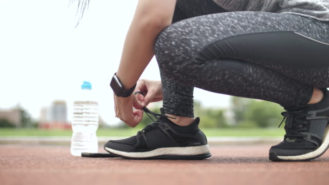 healthy women tying shoelaces on sports shoe - tighten stock videos and b-roll footage