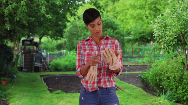 healthy young black woman in her garden removing gloves exhausted - gardening glove stock videos & royalty-free footage