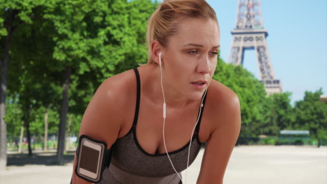 stockvideo's en b-roll-footage met healthy young blonde woman out running catching her breath near eiffel tower - zichtbare adem