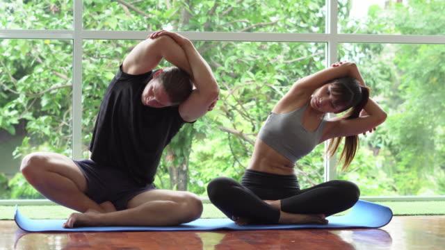 vídeos de stock, filmes e b-roll de ioga praticando dos pares novos saudáveis em casa - objeto manufaturado