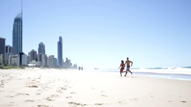vídeos y material grabado en eventos de stock de sano joven pareja corriendo en la playa - gold coast