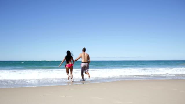 vídeos y material grabado en eventos de stock de sano joven pareja jugando en la playa - gold coast