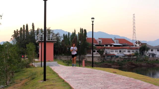 健康的な若い女性の公園でジョギング - アスレチック点の映像素材/bロール