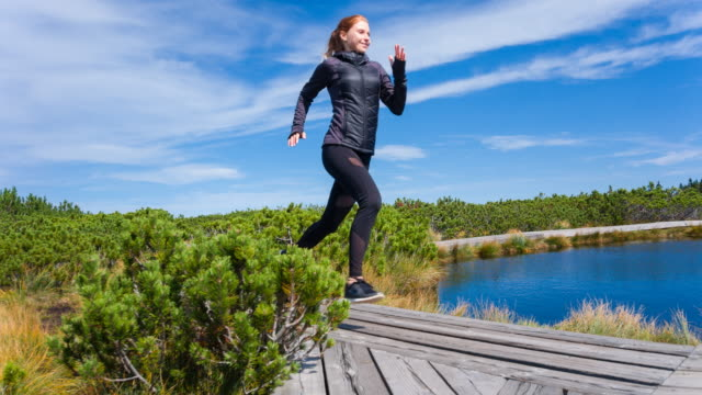 Healthy young woman jogging on a wooden pathway in nature