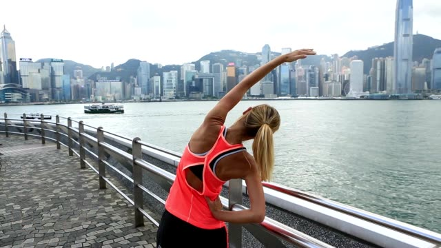 healthy young woman stretching muscles after morning run - tsim sha tsui stock videos & royalty-free footage