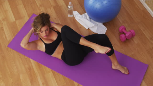 Healthy young woman working out in home gym