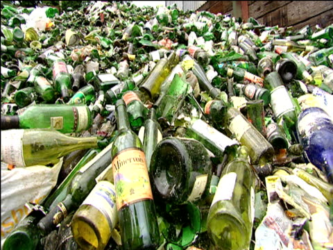 Heap of glass bottles for recycling tilt down to wine and beer bottles
