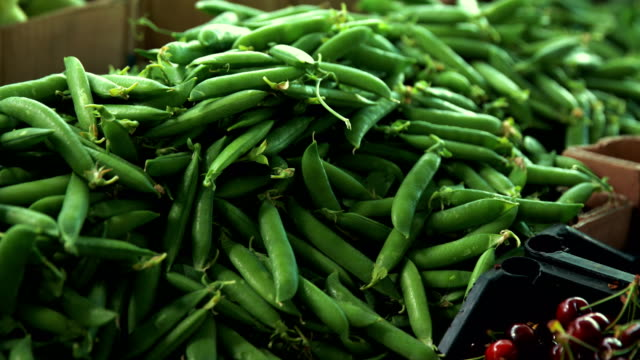 Heap of green peas in pods at grocery market
