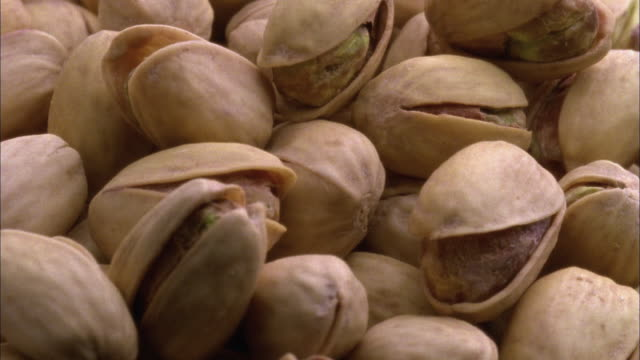 ecu, heap of pistachio nuts rotating - nutshell stock videos and b-roll footage