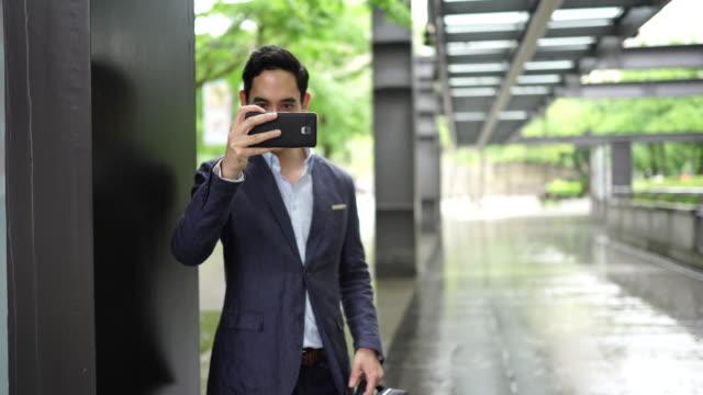 hörgeschädigter mann im anzug macht selfie mit handy - fotografieren stock-videos und b-roll-filmmaterial