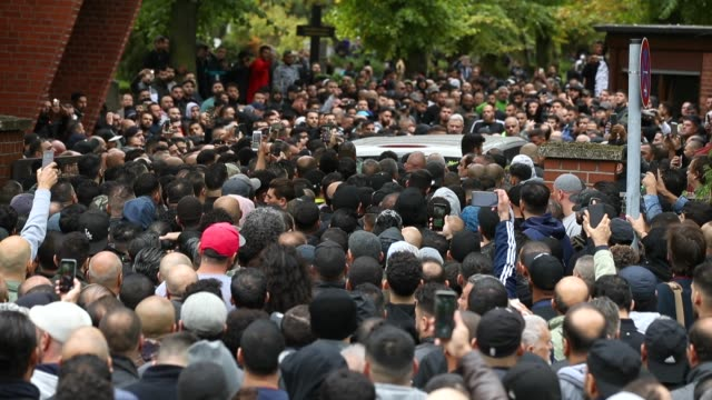 a hearse draped with a palstinian flag arrives carrying the body of nidal r an associate of a berlin arab clan through a crowd of mourners gathered... - killing people stock videos & royalty-free footage