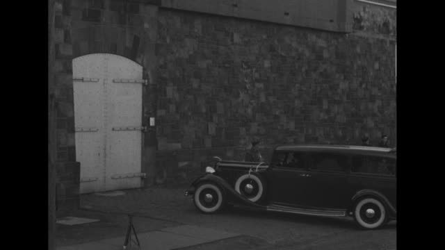 hearse drives down street next to prison and pulls up in front of closed gates / crowd starts to gather around hearse / two prison guards open gates,... - prison guard stock videos & royalty-free footage