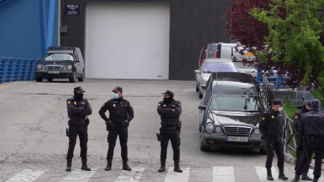 hearses arrive as police stand guard outside the palacio de hielo ice rink, temporarily converted into a morgue for victims of covid-19, in madrid,... - hielo stock-videos und b-roll-filmmaterial