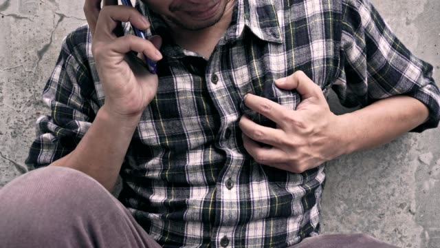 4K VIDEO: heart attack concept, a man clutching his chest while using phone to emergency calling.