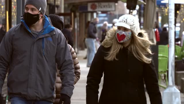 stockvideo's en b-roll-footage met heart design decorates a shopper's face mask worn outdoors during the holiday season in downtown ann arbor, michigan on december 23. while mask... - straatnaambord