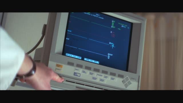 vidéos et rushes de cu heart machine monitor shows 'flatline', hand turns off machine - machinerie