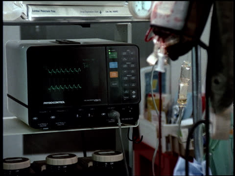 A heart monitor runs next to a bag of blood running into an iv in a  patient 's arm.