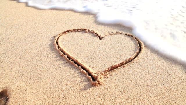 vídeos de stock, filmes e b-roll de coração na praia de areia excluído do mar - areia
