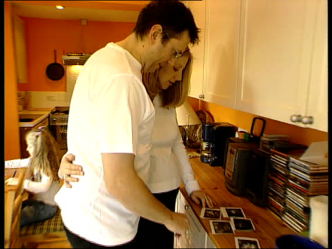 surrey carshalton cathy and mark proctor standing at kitchen counter as looking at scanned photographs of baby pull tcms photographs of ultrasound... - human uterus stock videos & royalty-free footage