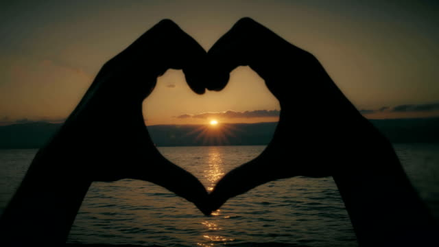 Heart shape hands. Sunset over water.