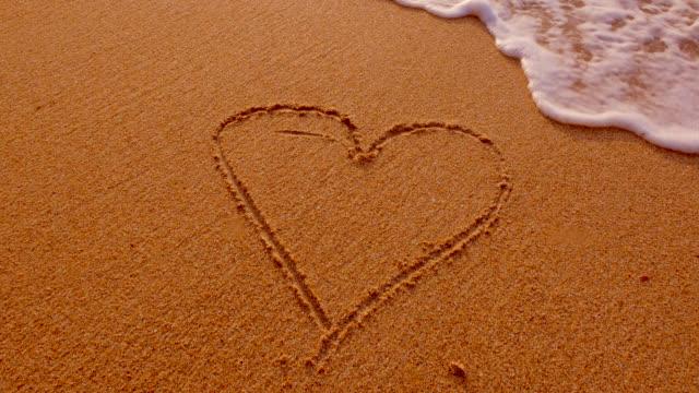 vidéos et rushes de forme de coeur dans le sable. - gomme