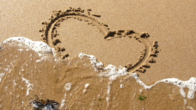 Heart shape in sand, washed away by tide.