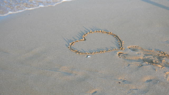 Heart shape in the sand washed away by the sea waves