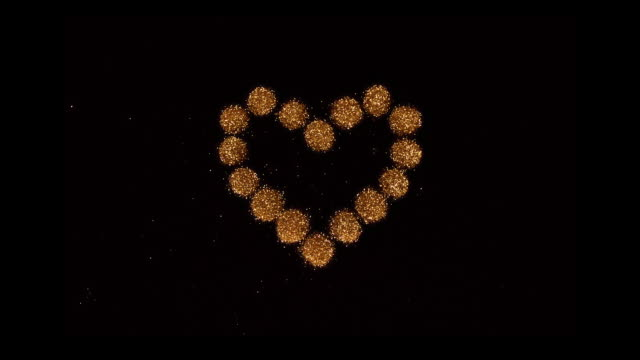 vidéos et rushes de heart shape made with gold glitter powder exploding towards camera and becoming defocused on black background, glittering bokeh - brillant