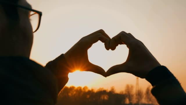 vídeos de stock, filmes e b-roll de coração em forma de ao pôr do sol - símbolo do coração