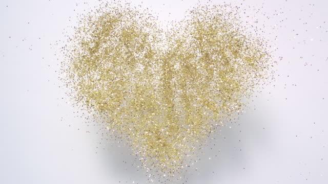 vídeos de stock e filmes b-roll de heart shaped gold glitter exploding towards camera and becoming defocused - coração