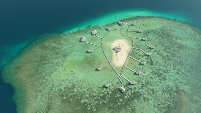 heart shaped overwater bungalow hotel resort on a tropical island sandbar and lagoon. - heart shape stock videos & royalty-free footage