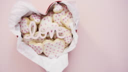 Heart shaped sugar cookies decorated with royal icing in gift box.
