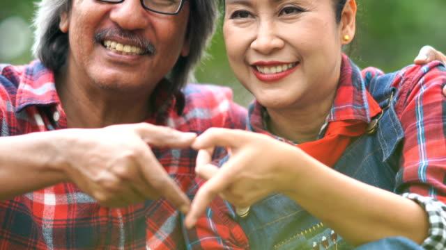 Heart sign by Asian senior couple  in garden