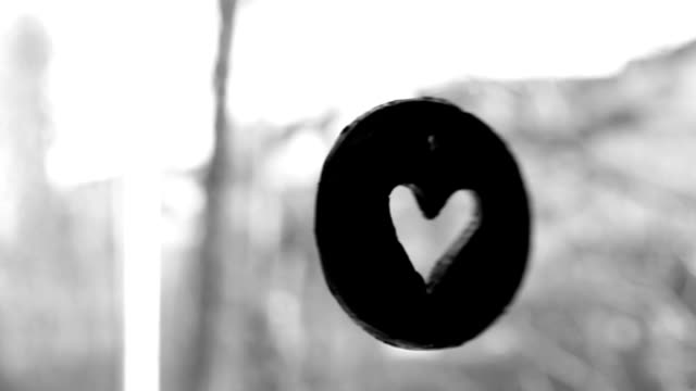 Heart symbol hangs on the window, black and white