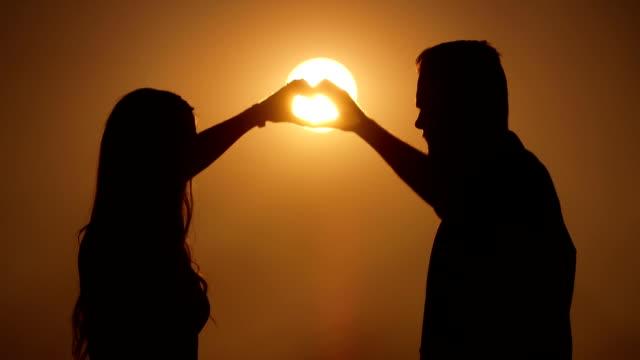 Herz-Symbol mit zwei Händen auf Sonnenuntergang Hintergrund
